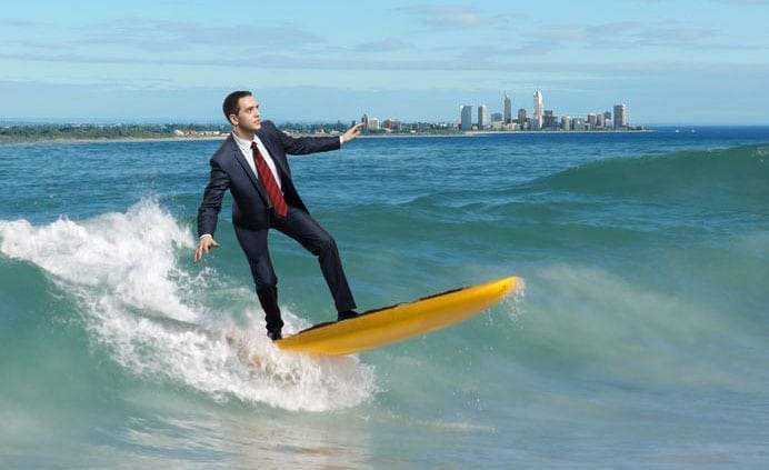 14107049 - image of young business person surfing on the waves of the ocean